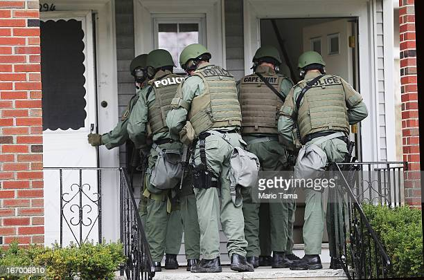 Team members go door-to-door searching for 19-year-old Boston Marathon bombing suspect Dzhokhar A. Tsarnaev on April 19, 2013 in Watertown,...