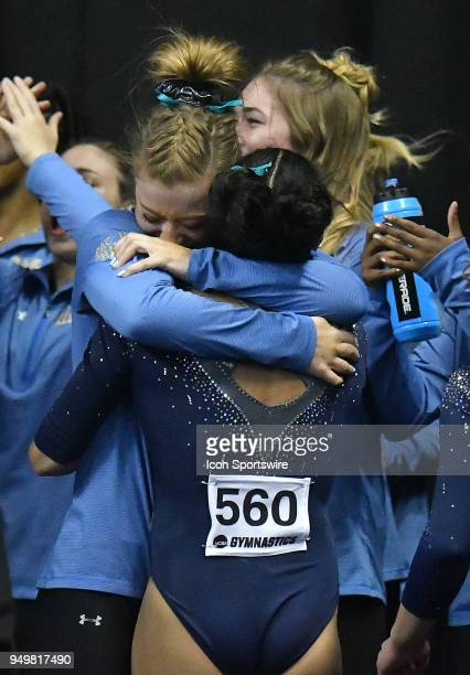 UCLA team members hug PengPeng Lee of UCLA who helped win the championship with a perfect score on the balance beam on the final event of the night...