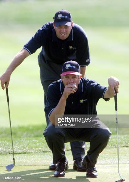 Team members Kirk Triplett and Stewart Cink line up a putt on the eighth hole during their four-ball match at the Robert Trent Jones Golf Club on the...