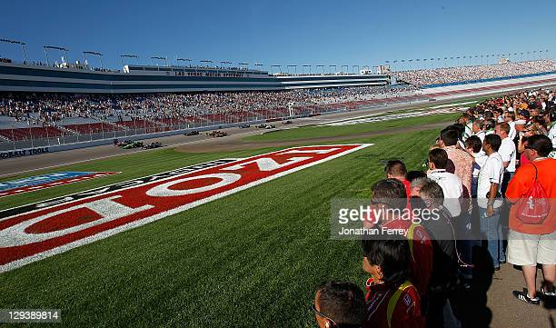 Team members line the pitlane as the drivers complete five memorial laps to honor Dan Wheldon, driver of the Dallara Honda, who died of injuries in a...