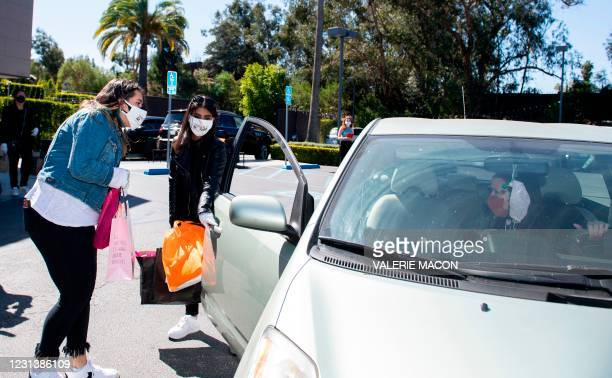 Team members load gifts bags in guests cars at the Luxe hotel during the drive-through gifting event organized by DPA Group president Nathalie...
