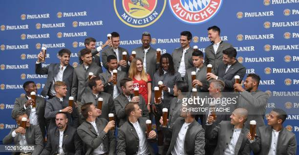 Team members of German first division football Bundesliga club FC Bayern Munich dressed in traditional Bavarian clothes and holding beer glasses are...