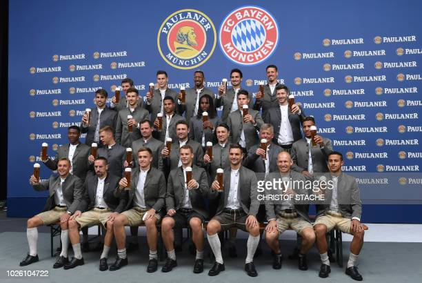Team members of German first division football Bundesliga club FC Bayern Munich dressed in traditional Bavarian clothes hold up beer glasses during a...