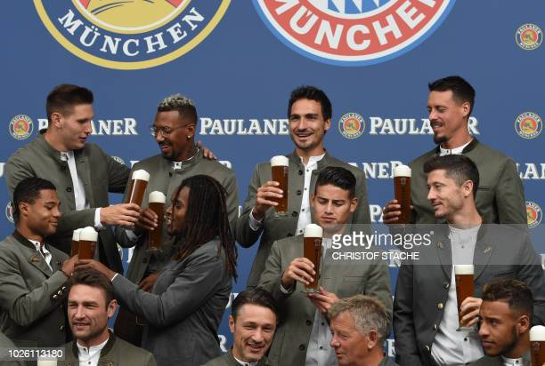 Team members of German first division football Bundesliga club FC Bayern Munich dressed in traditional Bavarian clothes clink their beer glasses...