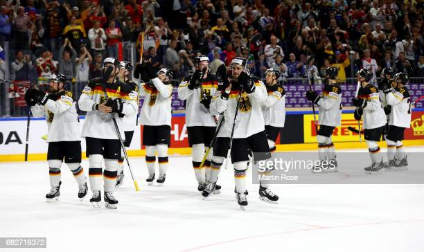 Team members of Germany celebrate victory after the 2017 IIHF Ice Hockey World Championship game between Italy and Germany at Lanxess Arena on May 13...
