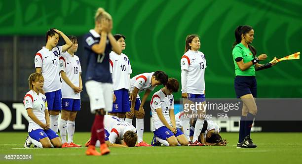 Team members of Korea Republic look dejected after losing the FIFA U20 Women's World Cup 2014 quater final match between France and Korea Republic at...