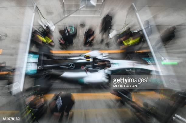 TOPSHOT Team members of Mercedes' British driver Lewis Hamilton practice a pit stop ahead of the Formula One Malaysia Grand Prix in Sepang on...