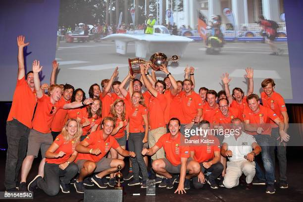 Team members of Nuon Solar Team vehicle 'Nuna9' from the Netherlands celebrate after receiving their trophy at the 2017 Bridgestone World Solar...