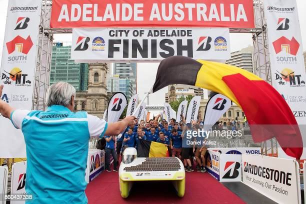 Team members of Punch Powertrain Solar Team vehicle 'Punch Two' from Belgium celebrate after crossing the finish line on Day 5 of the 2017...