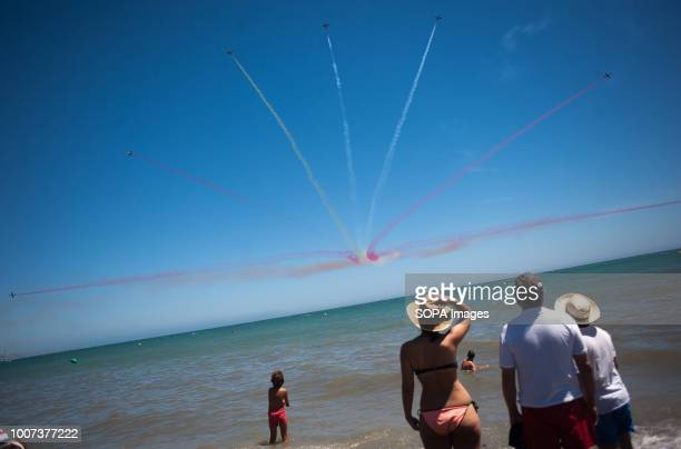 Team members of the Spanish Air Force 'Patrulla Aguila' perform on the air as people watch the event during the 2018 Torre del Mar International Air...