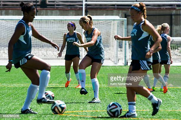 Team members of the University of Denver Pioneers are seen running through drills during a team practice at CIBER Field at the University of Denver...