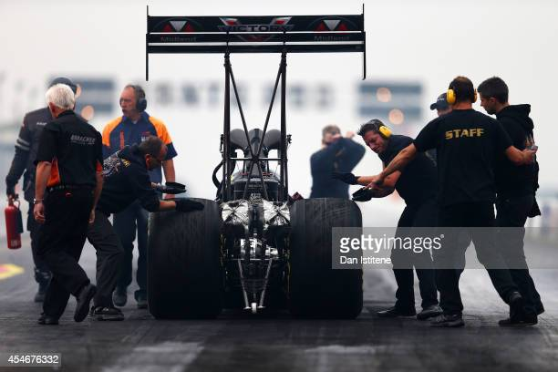 Team members scuff the car's tyres as they roll it back before launching a run during the Top Fuel Car qualifying for the European Drag Racing...
