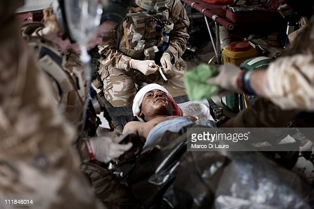 Team members treat onboard of the MERT CH47 Chinook helicopter an allegedly suspected Taliban fighter with fragmentation wounds to his neck left arm...