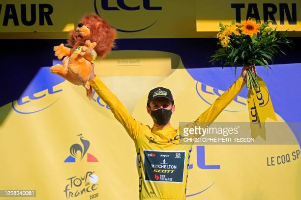Team Mitchelton rider Great Britain's Adam Yates celebrates his overall leader yellow jersey on the podium at the end of the 7th stage of the 107th...