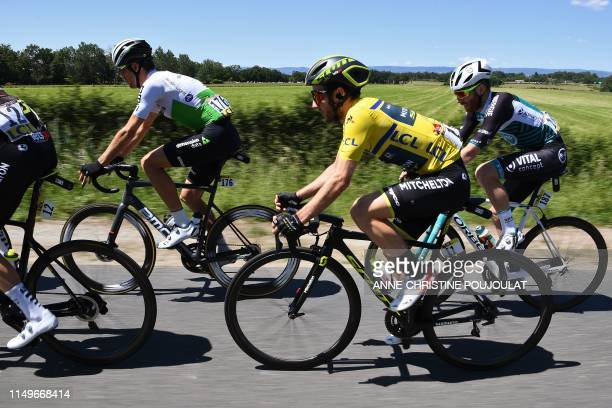 Team MitcheltonScott rider Great Britain's Adam Yates wearing wearing the overall leader's yellow jersey rides in the pack with Team Dimension Data...