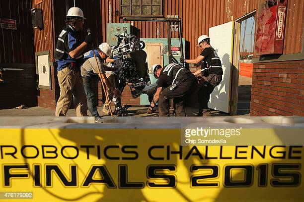Team MIT's Helios Atlas robot is carried back off the course after it fell during the Defense Advanced Research Projects Agency Robotics Challenge at...