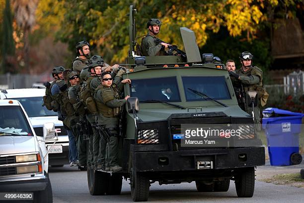 Team mobilizes on Gould Street as law enforcement stage outside a home after a mass shooting at the Inland Regional Center on December 2, 2105 in San...
