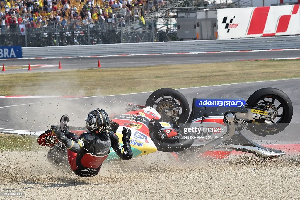 Team Moto2 Spanish rider Alex Pons falls with QMMF Racing team Belgiqn rider Xavier Simeon (unseen) during the Moto2 race of the San Marino Moto GP Grand Prix at the Marco Simoncelli Circuit in Misano, on September 11, 2016. / AFP / GIUSEPPE