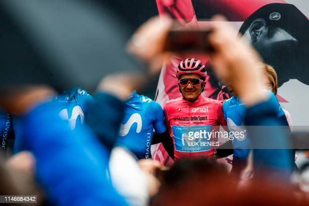 Team Movistar Ecuadorian Richard Carapaz wearing the overall leader's pink jersey poses for photographers at the start of the sixteenth stage of the...