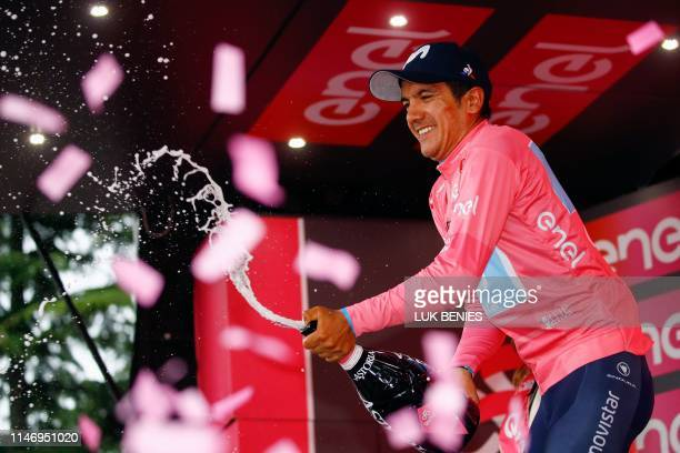 Team Movistar rider Ecuador's Richard Carapaz celebrates on the podium after winning the overall leader's pink jersey at the end of the stage...