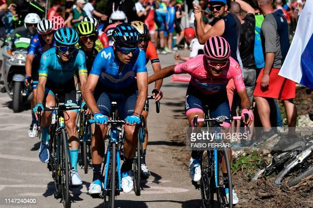 Team Movistar rider Ecuador's Richard Carapaz wearing the overall leader's pink jersey gestures as he takes a relay from fellow teammate Spain's...