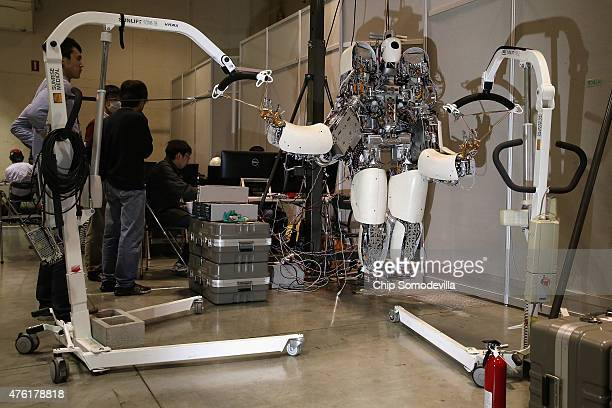 Team NEDOHydra's robot is held in place by racks inside the Robot Garage during the Defense Advanced Research Projects Agency Robotics Challenge at...