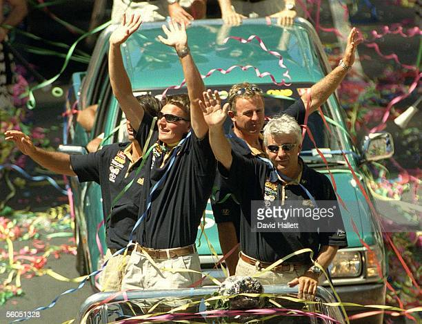 Team New Zealand's Dean Barker and Brad Butterworth wave to the thousands of fans who turned out for their victory parade down Queen Street following...