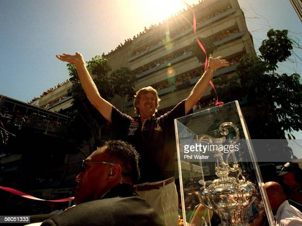 Team New Zealand''s Sir Peter Blake alongside a guarded America's Cup waves to the thousands of fans who turned out for their victory parade down...