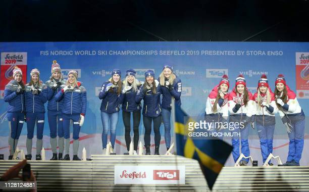 Team Norway with Heidi Weng Ingvild Flugstad Oestberg Astrid Unrenholdt and Therese Johaug celebrate their silver medals team Sweden with Ebba...
