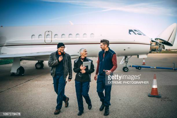 a team of aircraft mechanics walking away from a small private airplane with an opened nose cone parked on a taxiway - fuselage stock photos and pictures