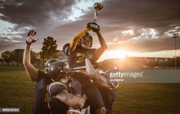 team of american football players celebrating victory at sunset. - squadra sportiva foto e immagini stock