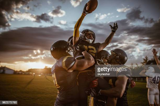 team of american football players celebrating victory at sunset. - football americano foto e immagini stock
