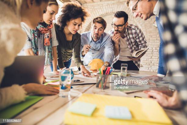 team of architects analyzing blueprints on a meeting in the office. - graphic designer stock pictures, royalty-free photos & images