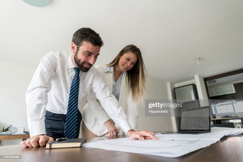 Team of architects at a business meeting discussing something while looking at a blueprint : Stock Photo
