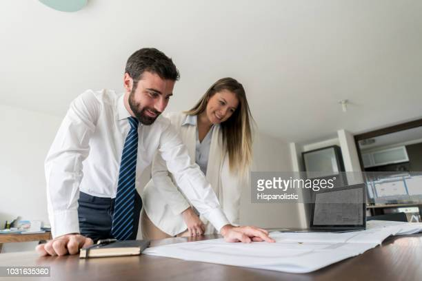 Team of architects at a business meeting discussing something while looking at a blueprint