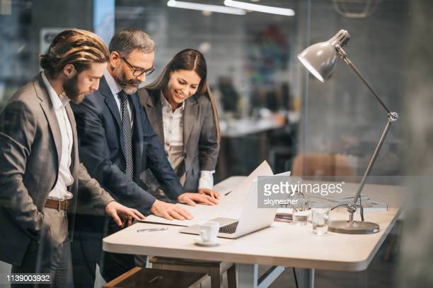 team of architects cooperating while analyzing blueprints in the office. - business plan stock pictures, royalty-free photos & images