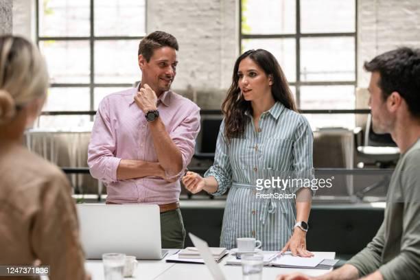 オープンスペースオフィスのスタンディングデスクを中心に会議で一緒に働く建築家/デザイナーチーム - 人間工学 ストックフォトと画像