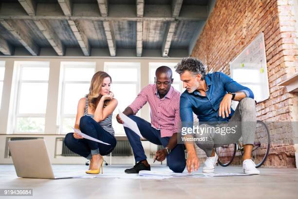 Team of architects discussing the rebuilding of a loft office