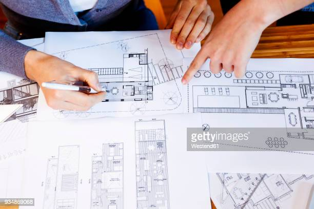 Team of architects working on a project, discussing blueprints