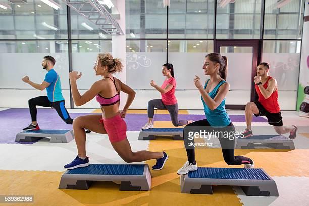 Équipe d'athlètes avoir étape entraînement dans une salle de sport.