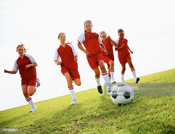 Team of athletic school children playing football in stadium