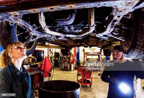 team of auto mechanics examining an old car - oil change stock pictures, royalty-free photos & images