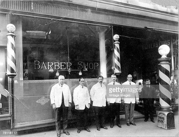 A team of barbers pose outside their shop early twentieth century Various signs including those on the barber poles advertise manicures massage and...