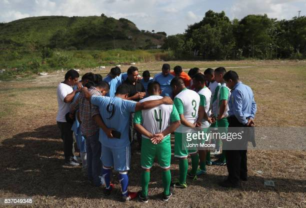 A team of Barrio 18 gang members and Honduran policemen huddle for a prayer before a soccer match on August 17 2017 in San Pedro Sula Honduras The...
