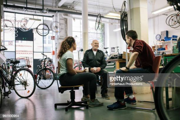Team Of Bike Mechanics Having Meeting In Workshop