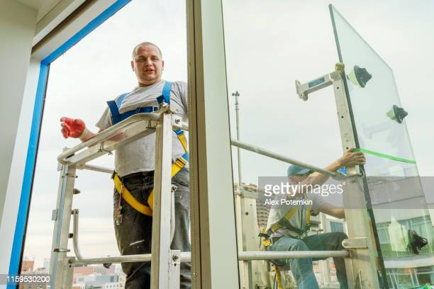 team of blue-collar workers replacing a broken window in the office building - applying a fresh sealant for a new glass installation. high-altitude work on the lifting platform which is placed outside. - replacement stock pictures, royalty-free photos & images