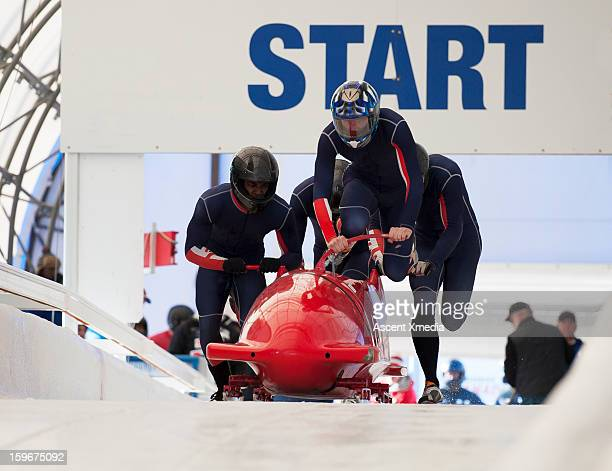 Team of bobsledders push bobsled out of start gate
