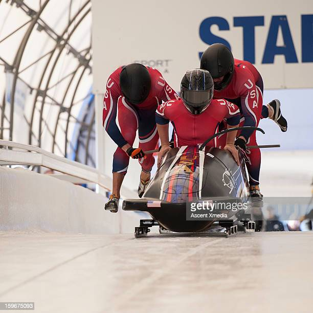 team of bobsledders push bobsled out of start gate - bobsledding stock pictures, royalty-free photos & images