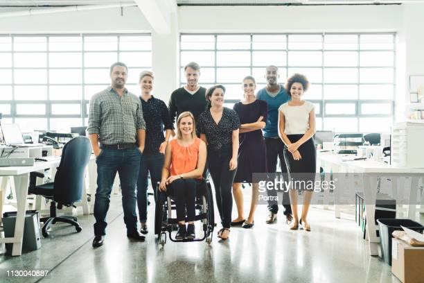 team of business people smiling in creative office - pessoas com deficiência imagens e fotografias de stock