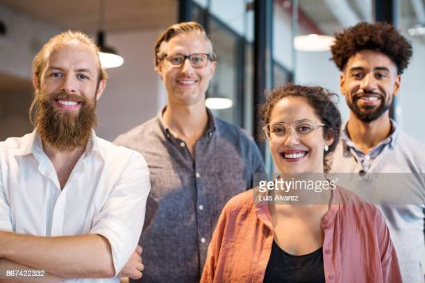 team of business people smiling in creative office - vier personen stockfoto's en -beelden